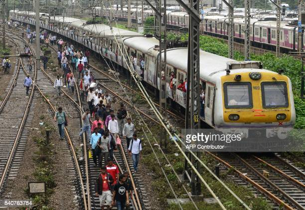 Indian commuters walk on railway tracks as train services slowly resume in Mumbai on August 30 after heavy rains brought major flooding to the...