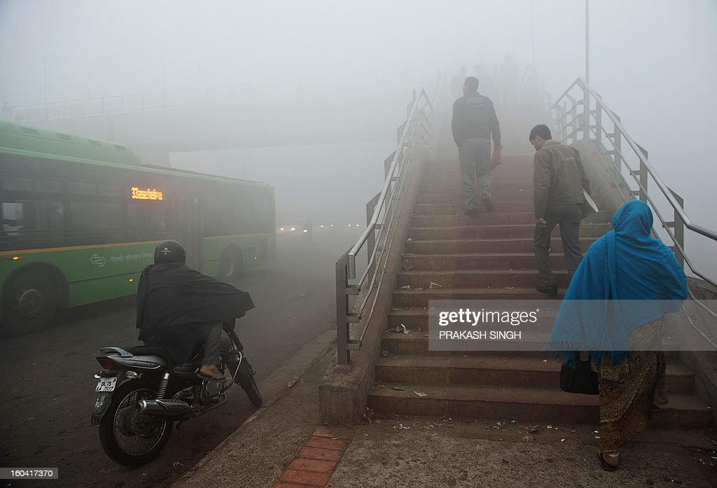 Indian commuters walk up a foot bridge as vehicles pass by early in New Delhi on January 31, 2013. Air Quality Index (AQI) pollution markers were at hazardous levels around the city. AFP PHOTO/ Prakash SINGH