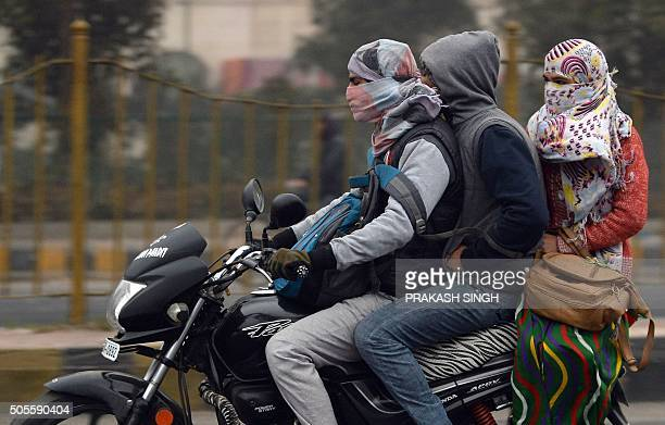 TOPSHOT Indian commuters wrapped in warm clothes share a motorcycle on a cold foggy morning in New Delhi on January 19 2016 AFP PHOTO / PRAKASH SINGH...