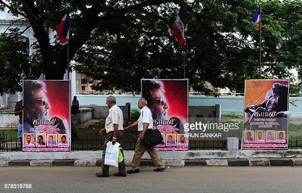 Indian commutners walk past hoardings of Indian movie star Rajinikanth ahead of the release of his Tamil movie 'Kabali' in Chennai on July 21 2016 As...