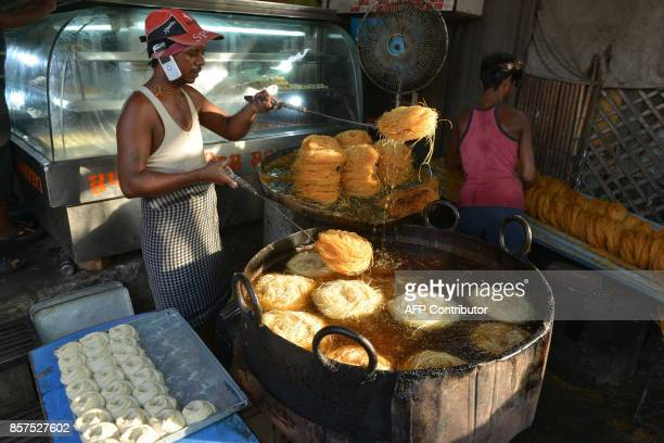 Indian confectioner prepare vermicelli outside of a sweet shop in Amritsar on October 4 2017 Traditionally sweets are purchased for the coming Karva...