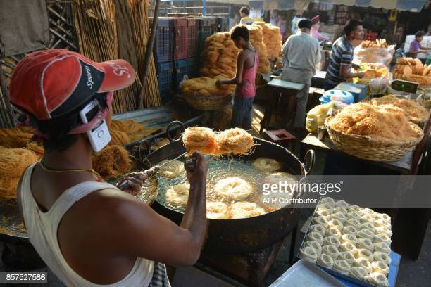 Indian confectioner prepares vermicelli outside of a sweet shop in Amritsar on October 4 2017 Traditionally sweets are purchased for the coming Karva...