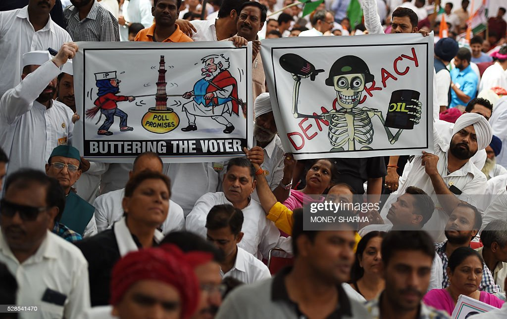 Indian Congress Party supporters hold placards and shout anti-government slogans ahead of a protest march in New Delhi on May 6, 2016. Former Indian prime minister Manmohan Singh, Congress Party President Sonia Gandhi and party Vice-president Rahul Gandhi were briefly arrested at a police station and later released during a 'Save Democracy' protest march against the ruling Bharatiya Janata Party (BJP). / AFP / MONEY