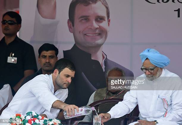 Indian Congress Party vicepresident Rahul Gandhi pours water for former prime minister of India Manmohan Singh during a rally in New Delhi on April...