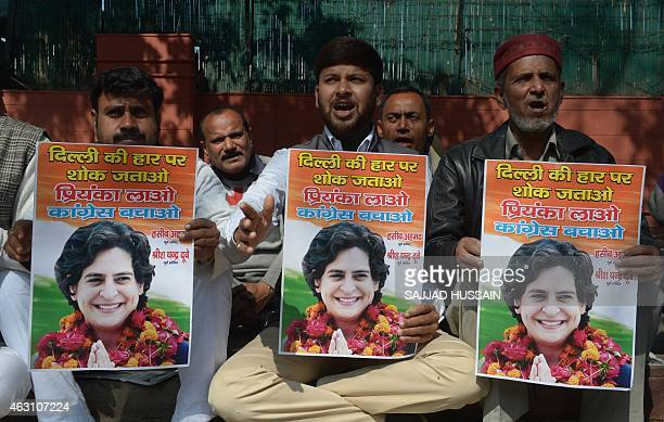 Indian Congress party workers hold pictures of Priyanka Gandhi as they shout slogans outside the All Indian Congress Committe office in New Delhi on...