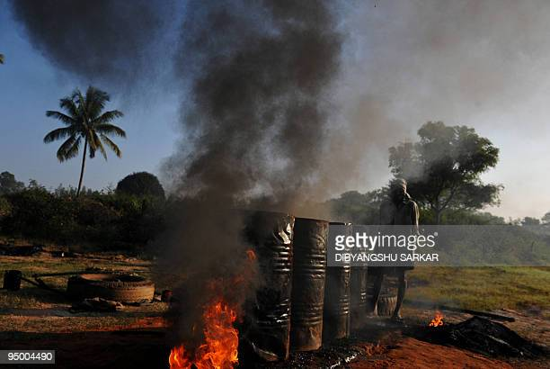 Indian construction labourers used tyre pieces to increase the heat for melting tar used for roads on the outskirts of Bangalore on December 10 2009...