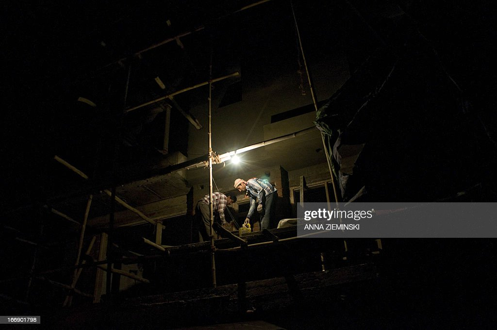 Indian construction labourers work into the night on a building site in New Delhi on April 18, 2013. India's inflation unexpectedly slipped to below six percent for the first time in over three years, official data April 15 showed, fanning hopes of fresh interest rate cuts to spur a flagging economy. AFP PHOTO/ Anna ZIEMINSKI