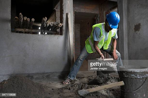 Indian construction worker mixing cement.