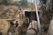 Indian construction workers from the state of Bihar prepare sections of a water line for welding at a fresh water storage project January 31 2008 in...