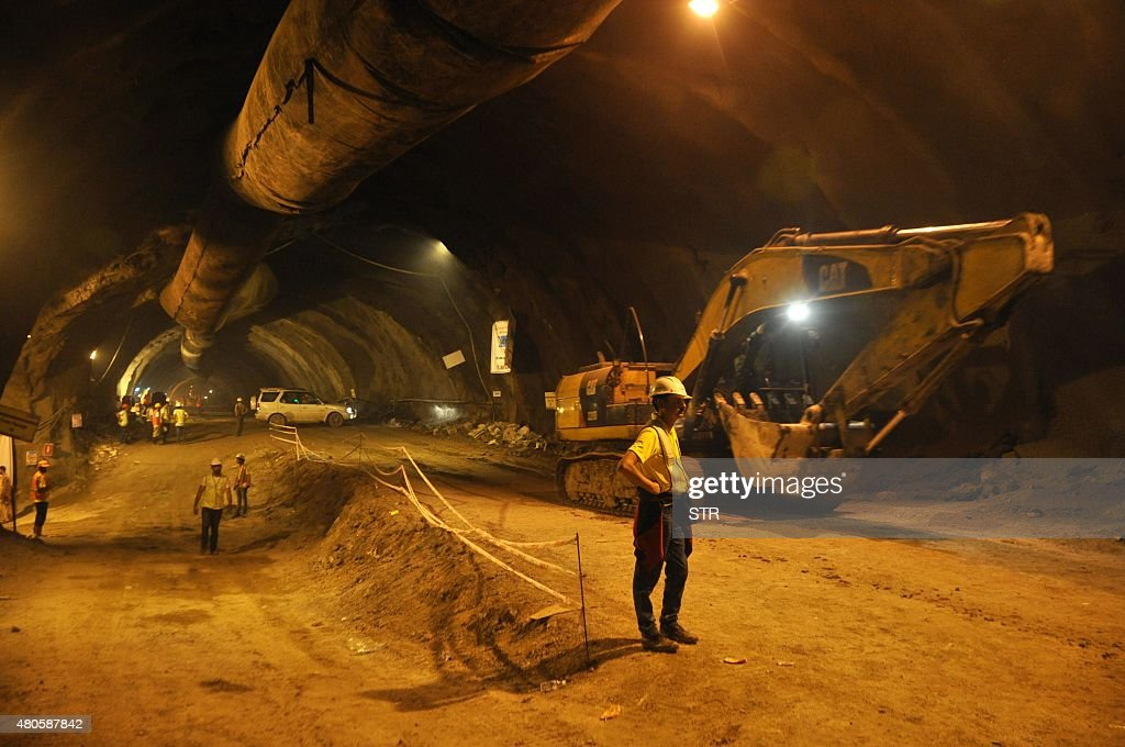 Indian construction workers gather in a tunnel that is part of the under-construction Jammu-Srinagar highway, in Chenani about 90 km from Jammu on July 13, 2015