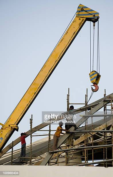 Indian construction workers labour at the underconstruction Jawaharlal Nehru Stadium in New Delhi on May 26 2010 The Nehru stadium is due to host the...