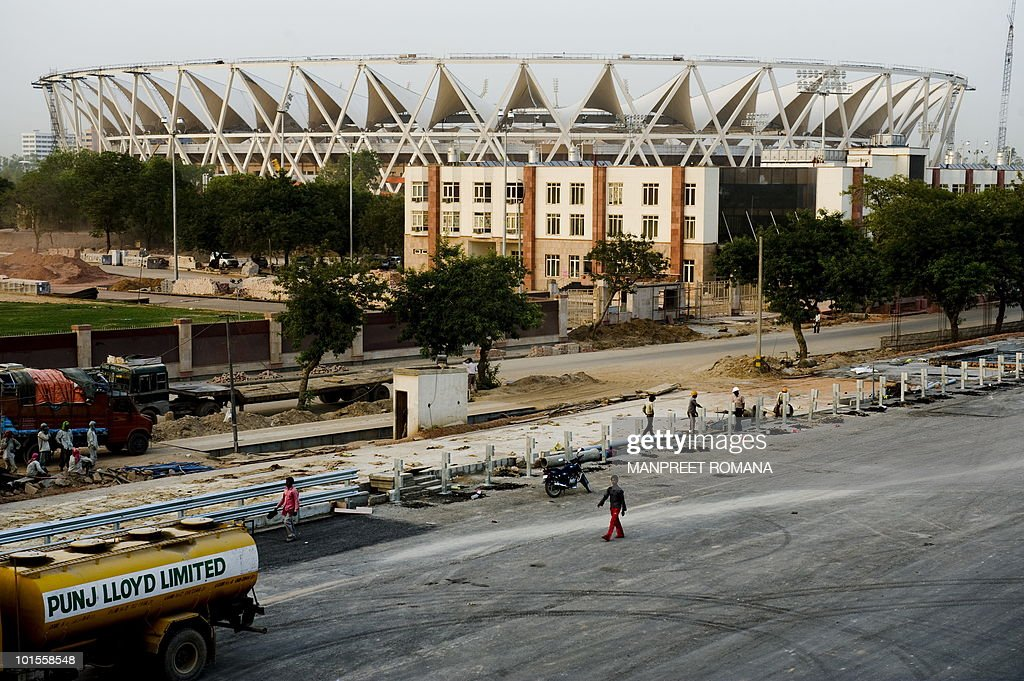 Indian construction workers walk at the under-construction Jawaharlal Nehru Stadium in New Delhi on May 26, 2010. The Nehru stadium is due to host the opening and closing ceremonies, besides the track and field events, at the October 3-14 Games in the Indian capital. The 12-day sporting extravaganza is being billed as the most expensive Commonwealth Games in history with an infrastructure and organising budget of two billion dollars. AFP PHOTO/Manpreet ROMANA
