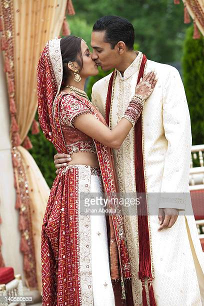 Indian couple in traditional wedding clothing, kissing