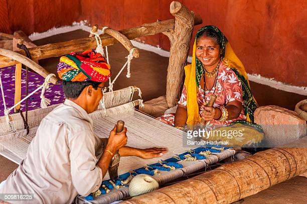 Indian couple making dhurry - colorful carpet