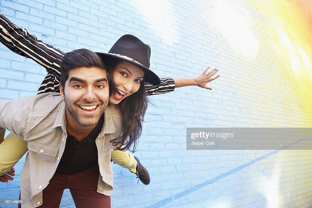 Indian couple piggybacking along brick wall