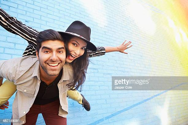 Indian couple piggybacking along brick wall