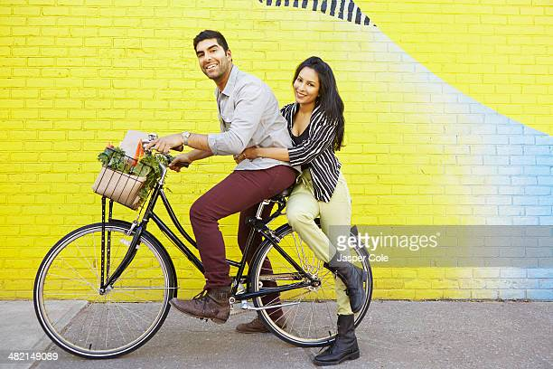 Indian couple riding bicycle on city street