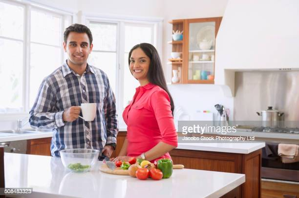 Indian couple smiling in kitchen