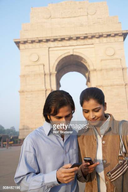 Indian couple using cell phone by India Gate, Delhi, India