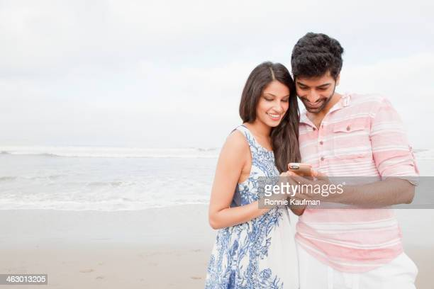 Indian couple using cell phone on beach