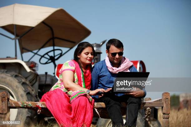 Indian couple using laptop in the field