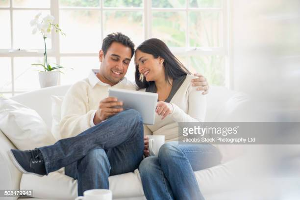 Indian couple using tablet computer on sofa