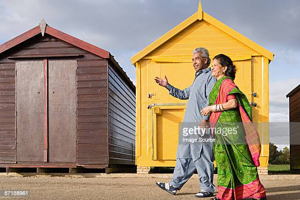 Indian couple walking by beach huts