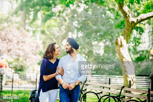 Indian couple walking in urban park