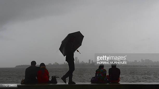 Indian couples enjoy the rain as they sit along the promenade on Marine Drive in Mumbai on June 17 2013 Heavy rains lashed parts of north India June...