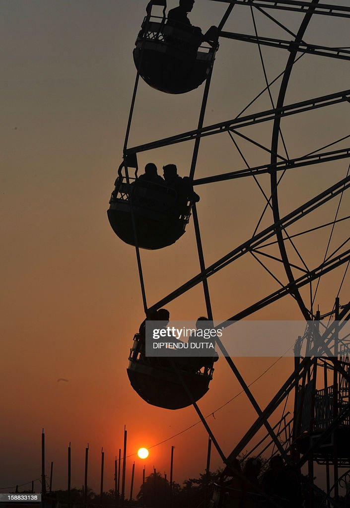 Indian couples ride a merry-go-round as the sunsets in Siliguri on December 31, 2012. Sydney will kick off a wave of dazzling firework displays welcoming in 2013, from Dubai to Moscow and London, with long-isolated Yangon joining the global pyrotechnics for the first time. AFP PHOTO/Diptendu DUTTA