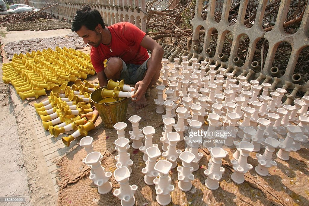 Indian craftsman paint earthen lamps ahead of the Hindu festival of Diwali in Amritsar on October 25, 2013. Diwali marks the victory of good over evil and commemorates the time when Hindu God Lord Rama achieved victory over Ravana and returned to his Kingdom Ayodhya after 14 years of exile. AFP PHOTO/ NARINDER NANU