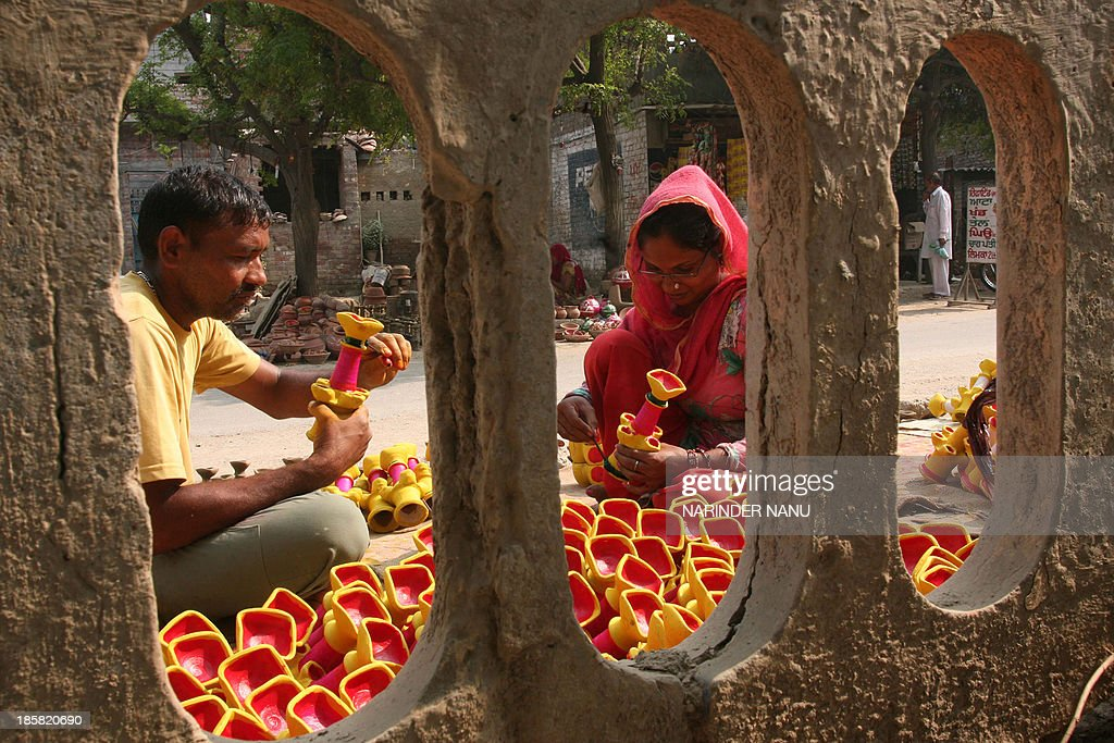 Indian craftsmen paint earthen lamps ahead of the Hindu festival of Diwali in Amritsar on October 25, 2013. Diwali marks the victory of good over evil and commemorates the time when Hindu God Lord Rama achieved victory over Ravana and returned to his Kingdom Ayodhya after 14 years of exile.