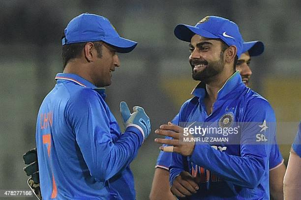 Indian cricket captain Mahendra Singh Dhoni celebrates with his teammate Virat Kohli after winning the third ODI cricket match between Bangladesh and...