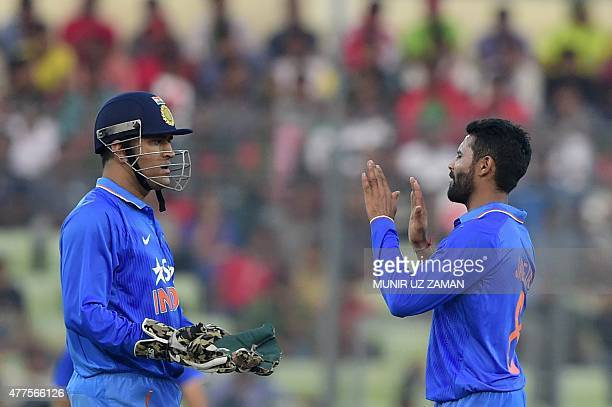 Indian cricket captain Mahendra Singh Dhoni congratulates teammate Ravindra Jadeja after the dismissal of unseen Bangladesh batsman Sabbir Rahman...