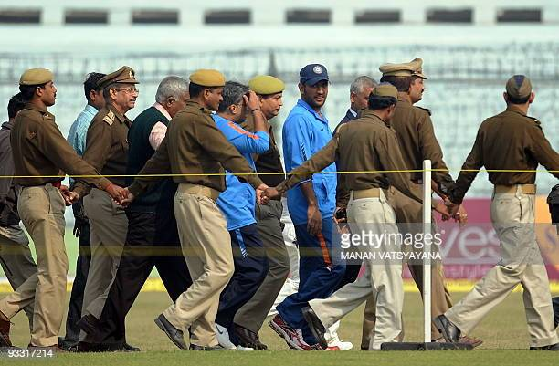 Indian cricket captain Mahendra Singh Dhoni is escorted by police officials after a training session at the Green Park Stadium in Kanpur on November...