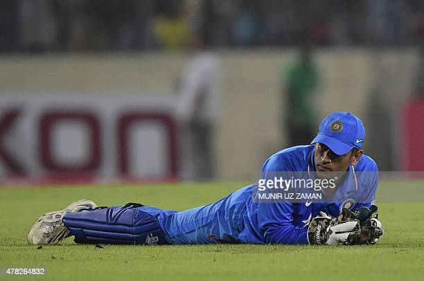 Indian cricket captain Mahendra Singh Dhoni looks on during the third ODI cricket match between Bangladesh and India at the ShereBangla National...