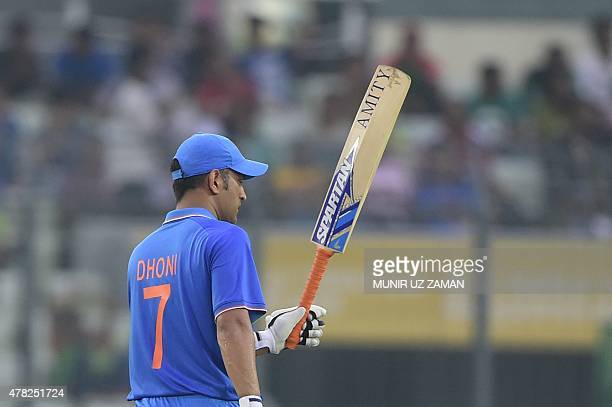 Indian cricket captain Mahendra Singh Dhoni reacts after scoring a half century during the third ODI cricket match between Bangladesh and India at...