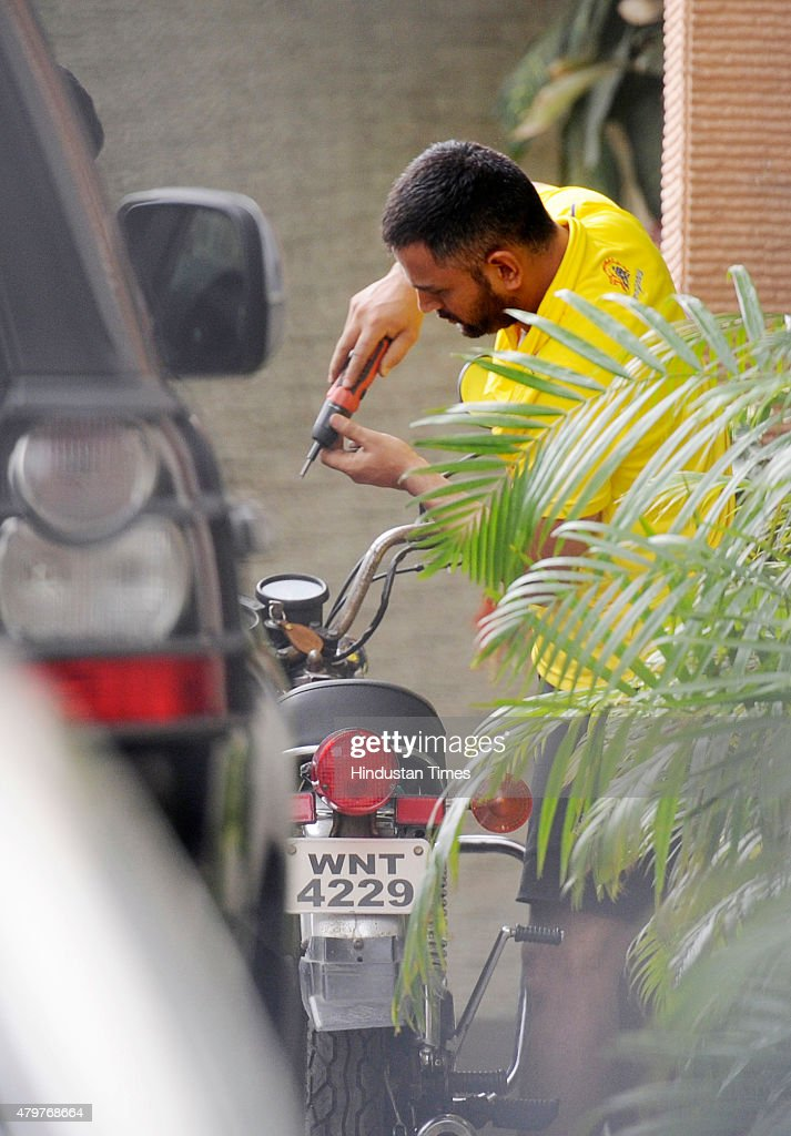 Indian cricket captain Mahendra Singh Dhoni repairing his motorcycle on his 34th birthday at his house Saurya Harmu Housing Colony on July 7 2015 in...