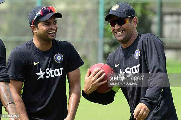 Indian cricket captain Mahendra Singh Dhoni shares a light moments with his teammate Suresh Raina during a practice session at the ShereBangla...