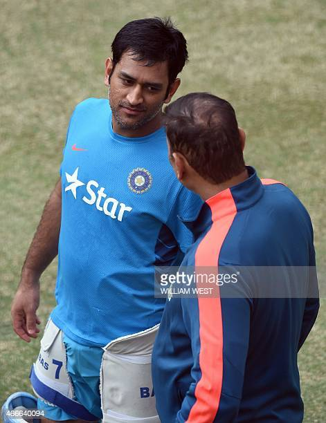 Indian cricket captain Mahendra Singh Dhoni speaks with team management member Ravi Shastri during a training session ahead of their 2015 Cricket...