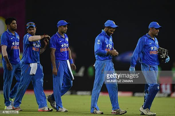 Indian cricket captain Mahendra Singh Dhoni walks off with his teammates after winning the third ODI cricket match between Bangladesh and India at...