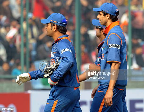 Indian cricket captain Mahendra Singh Dhoni walks with teammates back to the pavilion after the cancellation of the fifth and final One Day...