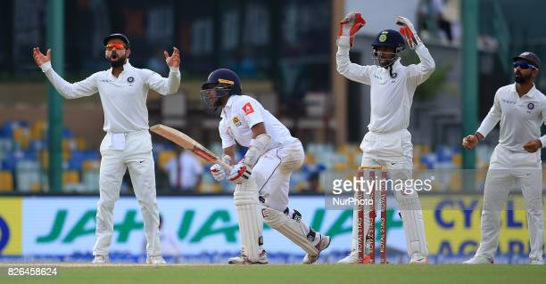 Indian cricket captain Virat Kohli and Indian wicket keeper Wriddhiman Saha appeals unsuccessfully as Sri Lankan cricketer Kusal Mendis looks on...
