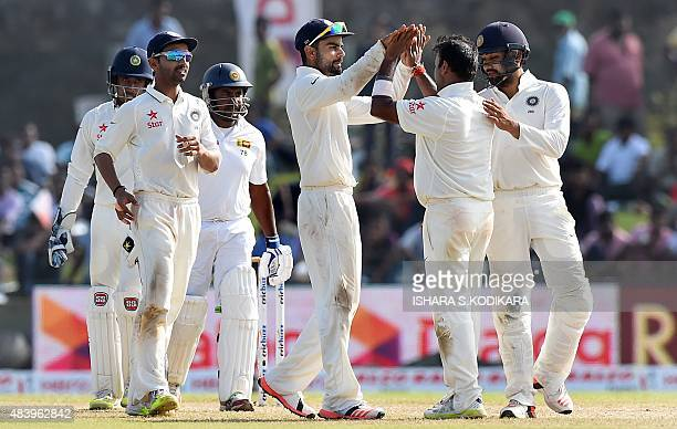 Indian cricket captain Virat Kohli and teammates celebrate the dismissal of Sri Lankan cricketer Rangana Herath during the third day of the opening...