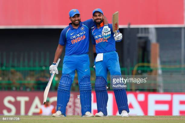 Indian cricket captain Virat Kohli celebrates after scoring 100 runs as Rohit Sharma joins in during the 4th One Day International cricket match...