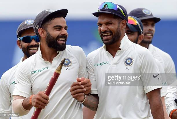 Indian cricket captain Virat Kohli celebrates with his teammate Shikhar Dhawan after victory in the third day of the third and final Test match...