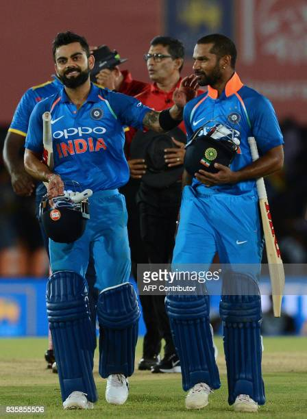 Indian cricket captain Virat Kohli celebrates with his teammate Shikhar Dhawan after victory in the first One Day International cricket match between...