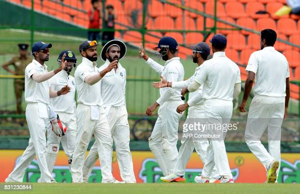 Indian cricket captain Virat Kohli celebrates with his teammates after dismissing Sri Lankan cricketer Dilruwan Perera during the third day of the...