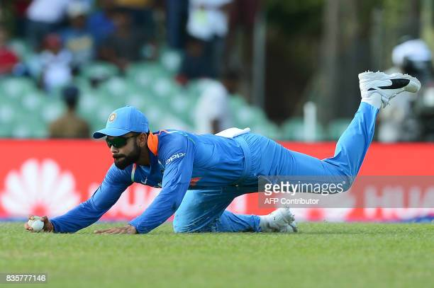 Indian cricket captain Virat Kohli dives as he attempts to field a ball during the first One Day International cricket match between Sri Lanka and...