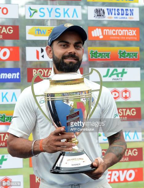 Indian cricket captain Virat Kohli gestures as he holds the trophy after victory in the third day of the third and final Test match between Sri Lanka...
